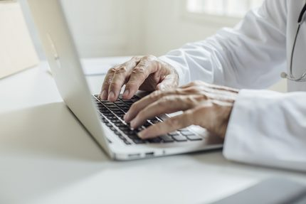 Hands of unrecognisable doctor sitting at his office and typing on his laptop.